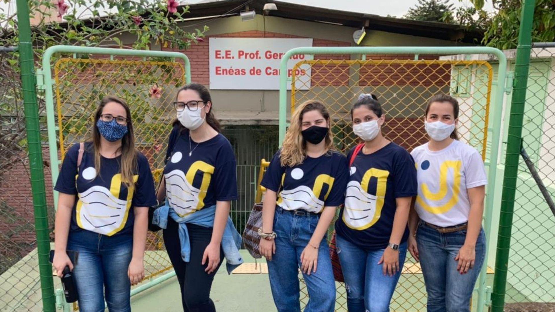 A imagem mostra as quatro alunas responsáveis pelo projeto e a orientadora pedagógica em frente a escola estadual.