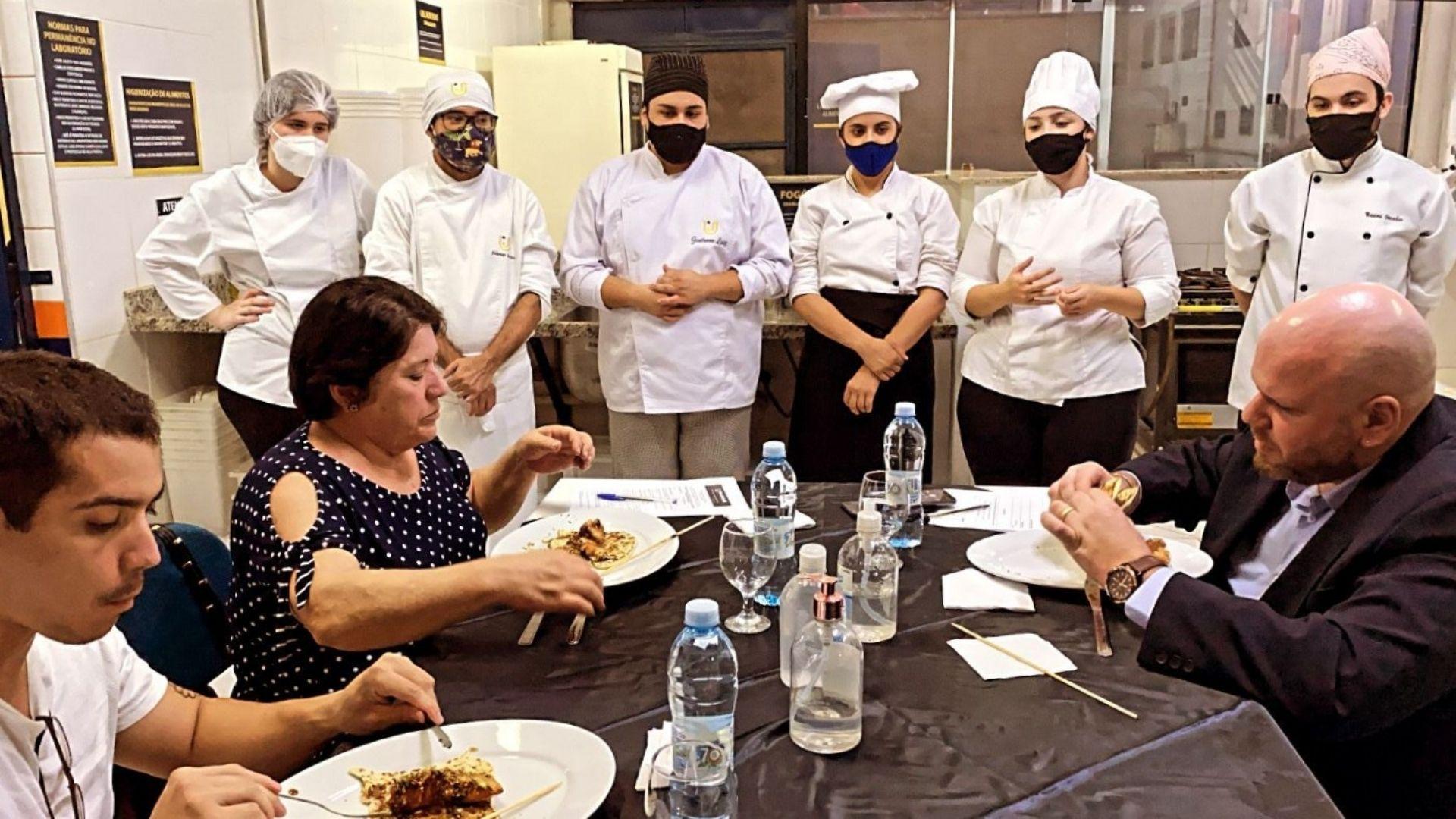 A imagem mostra a bancada avaliadora do Evento Gastronômico Pedagógico provando pratos criados pelos alunos.