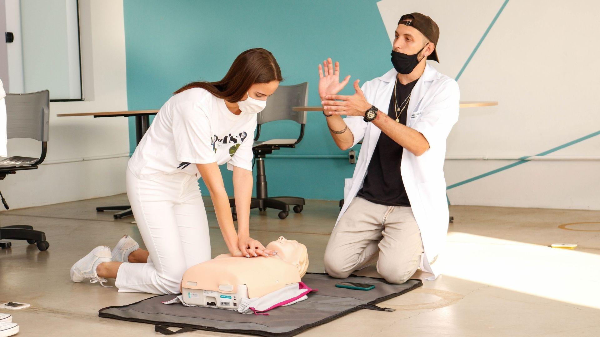"""A imagem mostra uma atividade da """"Experiência Medicina"""", uma visitante aprende técnicas de massagem cardíaca."""